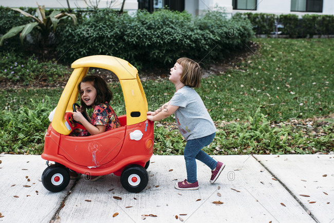 Girls playing together outside with toy car
