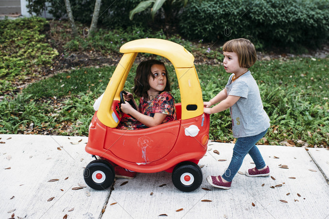 A little girl pushes her big sister in a toy car