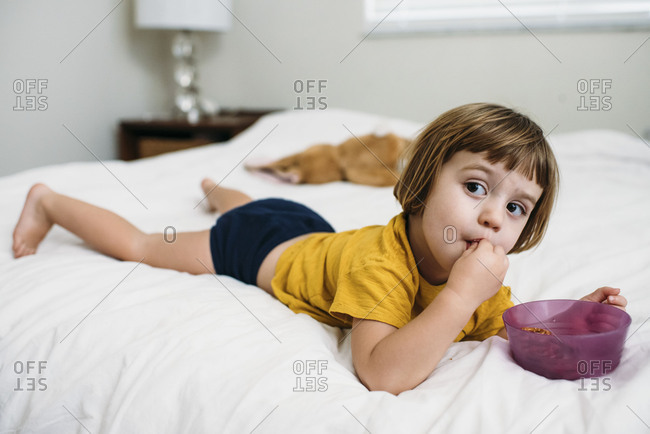 Toddler girl lying on bed eating a snack