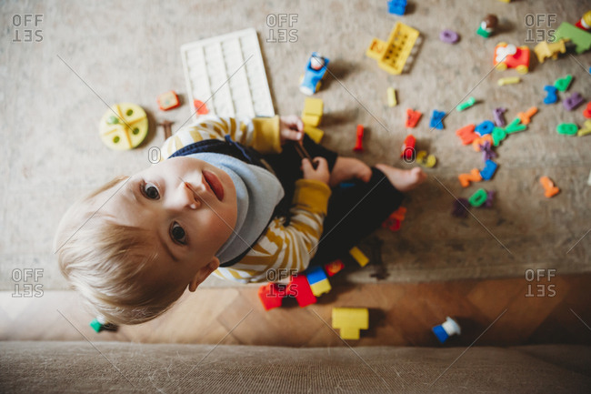 Overhead portrait of cute baby boy with toys sitting on carpet at home