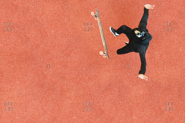 High angle view of man skateboarding on orange floor at skateboard park