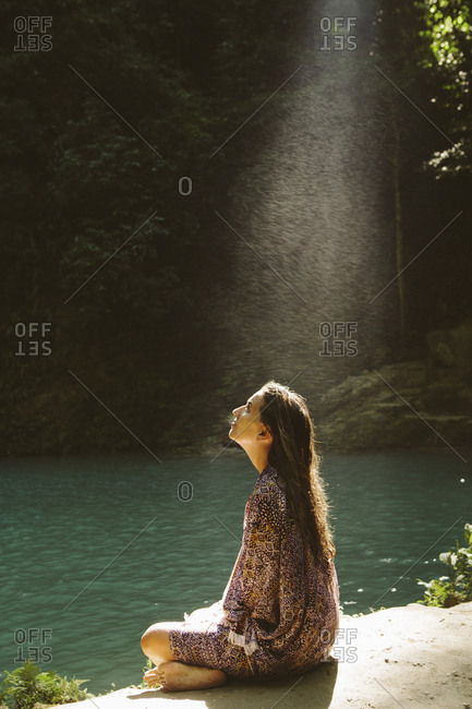 Side view of thoughtful woman sitting by river in forest