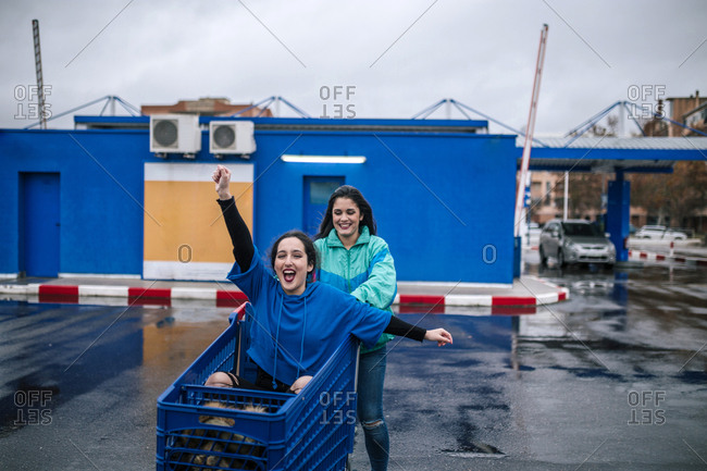 Woman pushing friend sitting in shopping cart on wet street against sky