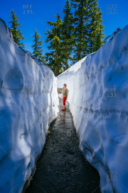 Senior woman standing in narrow walkway amidst ice at Crater Lake National Park
