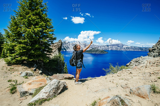 Side view of female hiker taking selfie while standing against Crater Lake