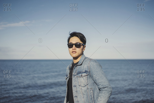 Young man wearing sunglasses and denim jacket while standing against sea and sky