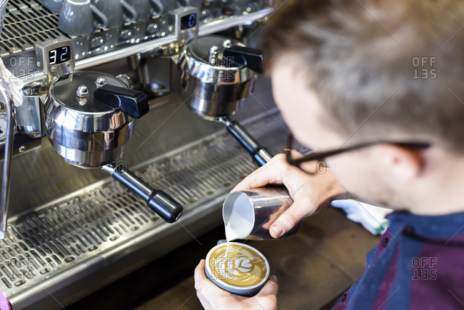 Barista pouring milk in coffee while making frothy drink at cafe