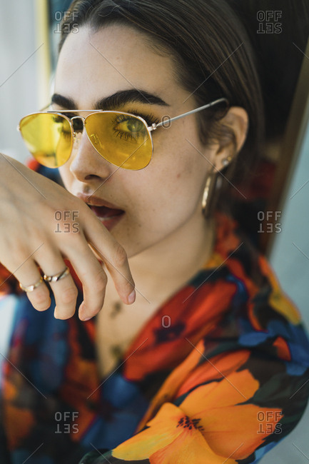 Portrait of confident young woman wearing sunglasses at home