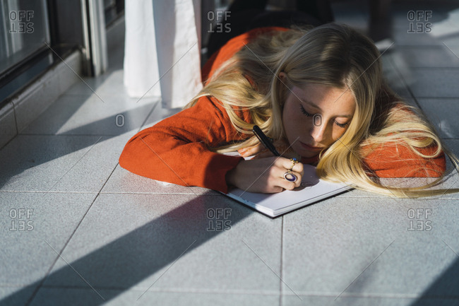Young woman sketching on book while lying on tiled floor at home