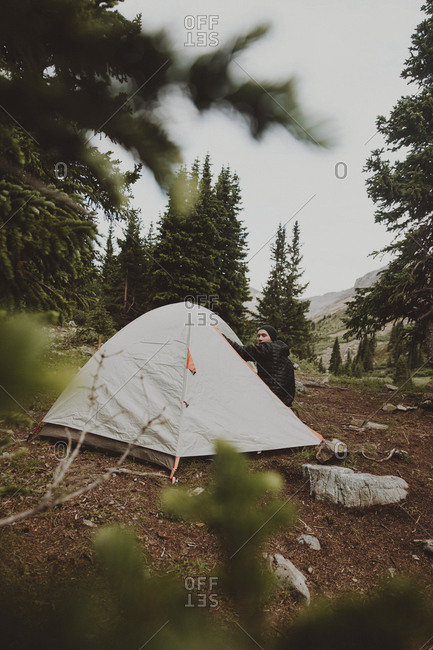 Hiker by tent at forest