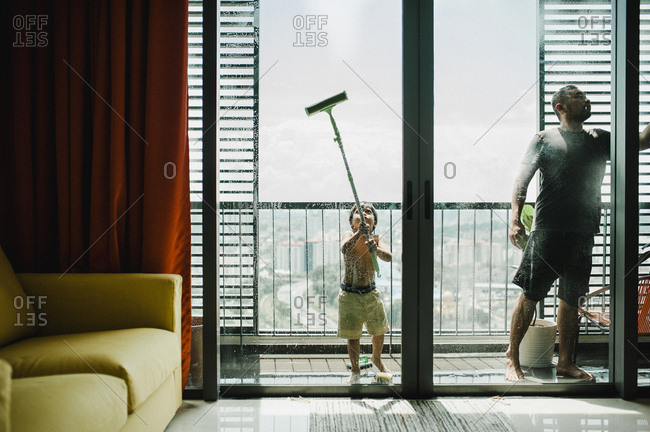 Father and son cleaning windows in balcony seen through glass