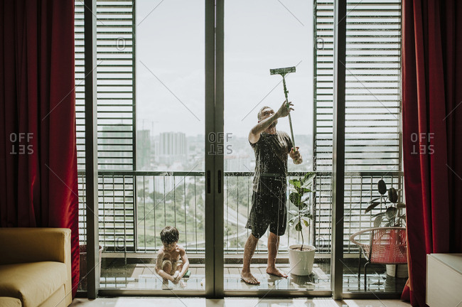 Father with son cleaning windows in balcony seen through glass