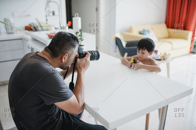 Father photographing son playing with toy while sitting by table at home