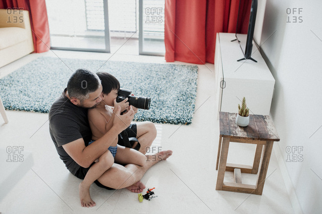 High angle view of father with son photographing while sitting on floor at home