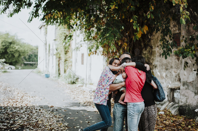 Happy family embracing while standing on street