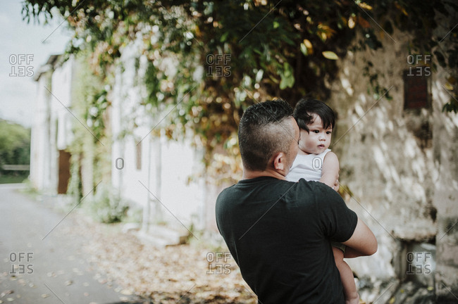 Rear view of father carrying son while standing on street