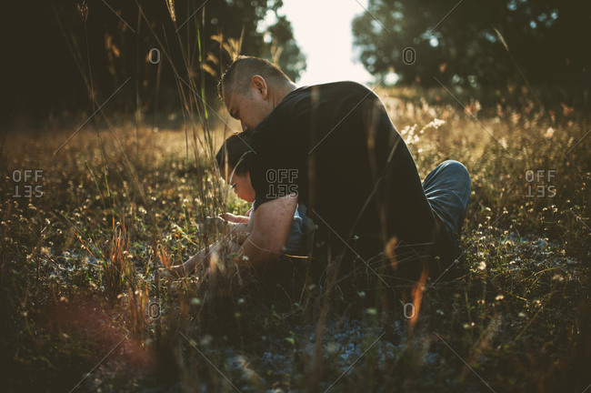 Rear view of father with son sitting on grassy field