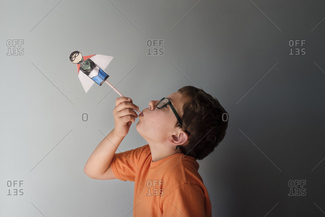 Side view of boy playing with superhero toy against wall at home