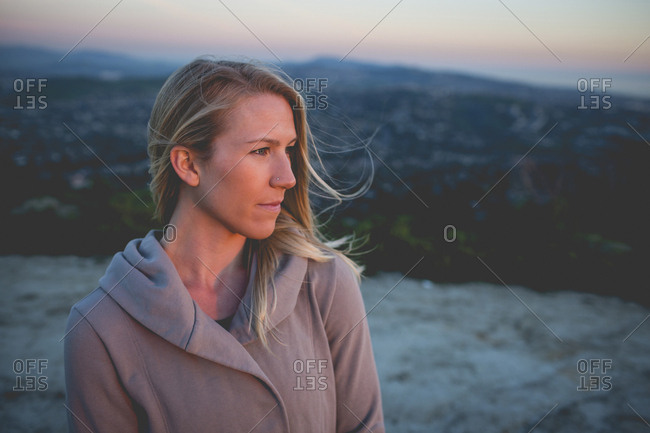 High angle view of thoughtful woman standing on mountain against sky during sunset