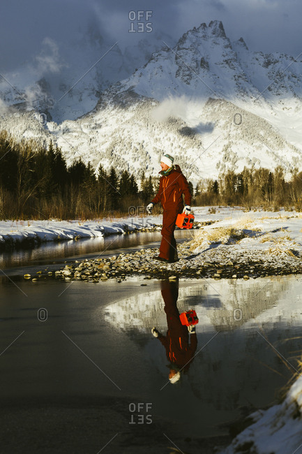 Full length of man standing by lake against snowcapped mountains