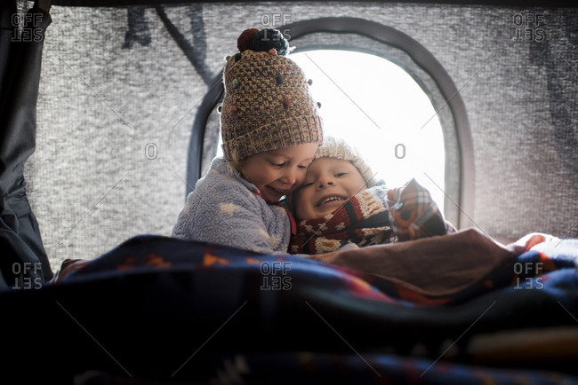 Smiling siblings sitting in roof tent