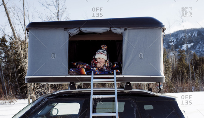 Portrait of smiling boy sitting in roof tent on car