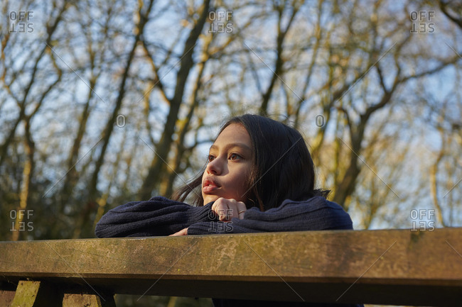 Low angle view of thoughtful girl looking away while standing by railing at park
