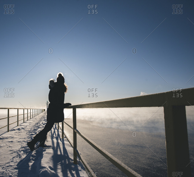 Full length of woman standing on snow covered pier by railing over frozen lake against sky