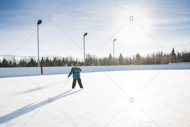 Rear view of boy ice-skating on snow against sky
