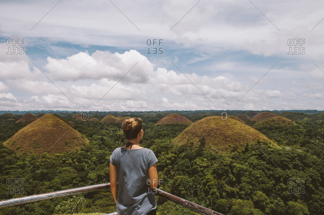Rear view of woman looking at Chocolate Hills while standing by railing against cloudy sky