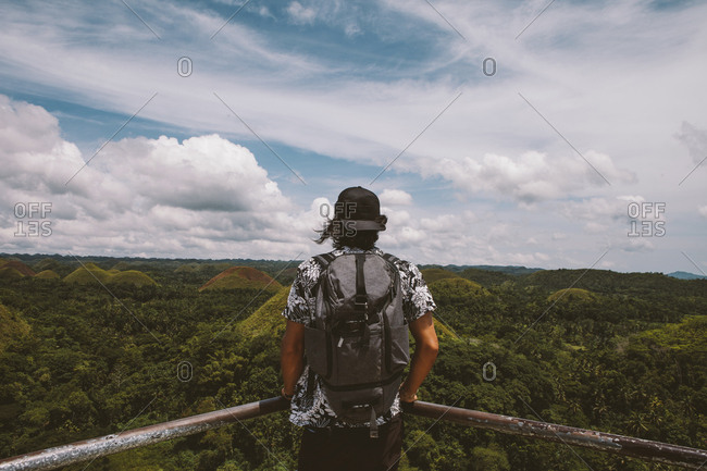 Rear view of man with backpack looking at Chocolate Hills while standing by railing