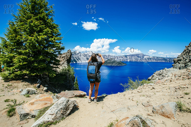 Rear view of female hiker with backpack photographing while standing against Crater Lake