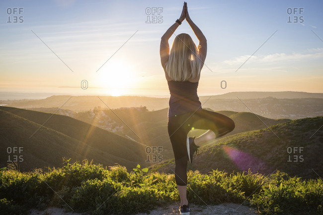 Rear view of woman exercising on mountain against sky during sunset