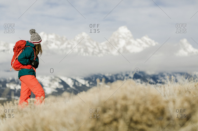Female hiker with backpack looking at view against snowcapped mountains