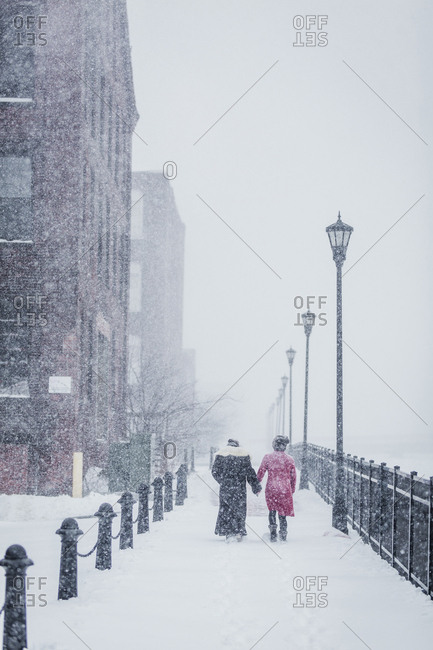 Rear view of female friends walking amidst railings in city during snowfall