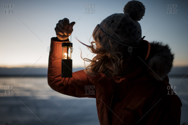 Woman holding illuminated lantern while standing on snow covered field during sunset
