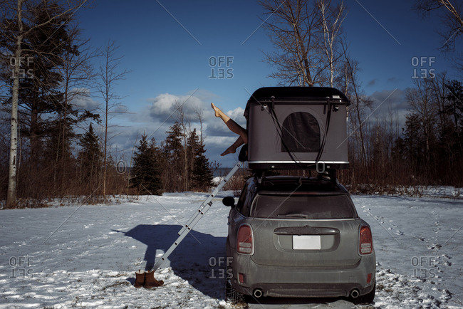 Low section of woman sitting in roof tent on car