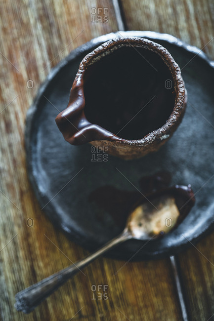 High angle close-up of chocolate syrup in container with spoon on table