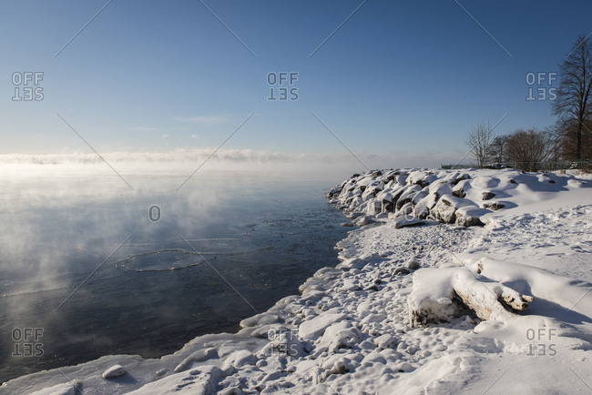 Scenic view of frozen lake against sky during foggy weather