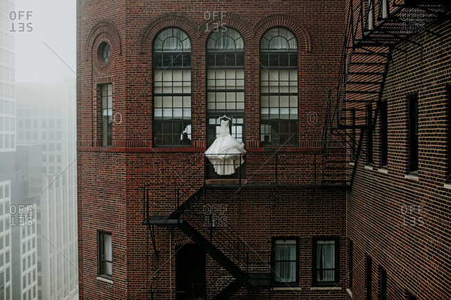 Wedding dress hanging by fire escape of building in city