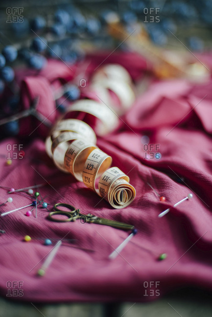 Close-up of scissors, straight pins and tape measure on dress