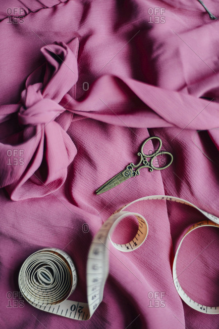 High angle view of scissors and tape measure on dress