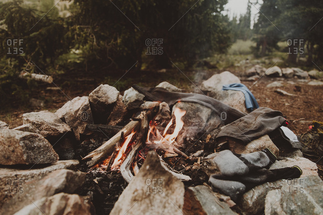 Textiles by burning campfire amidst rocks in forest