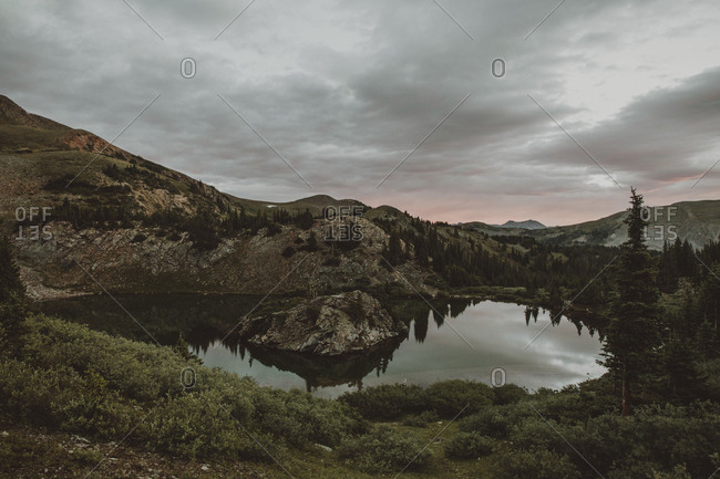 Scenic view of lake by mountains against cloudy sky during dusk