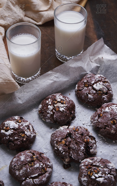 High angle view of chocolate cookies in baking sheet by milk on table