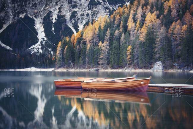 Boats moored at Lake Landro by mountains during autumn
