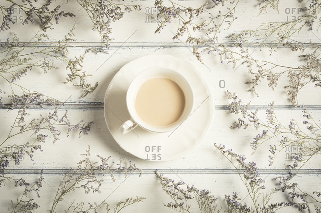 Overhead view of coffee cup amidst flowers on wooden table