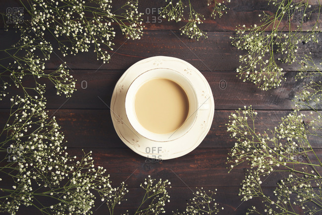 Overhead view of coffee cup amidst baby's-breath flowers on wooden table