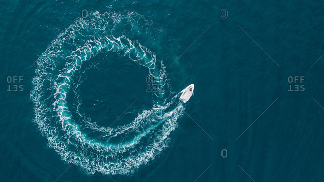 Aerial view of a boat driving in circle in the sea