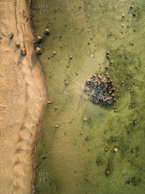Abstract aerial view of stones in greenish water in Estonia